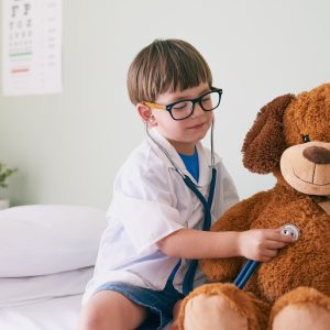 Shot of a little boy pretending to be a doctor while examining his teddybear