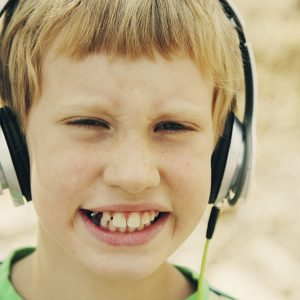 Portrait of cute autistic boy with headphones